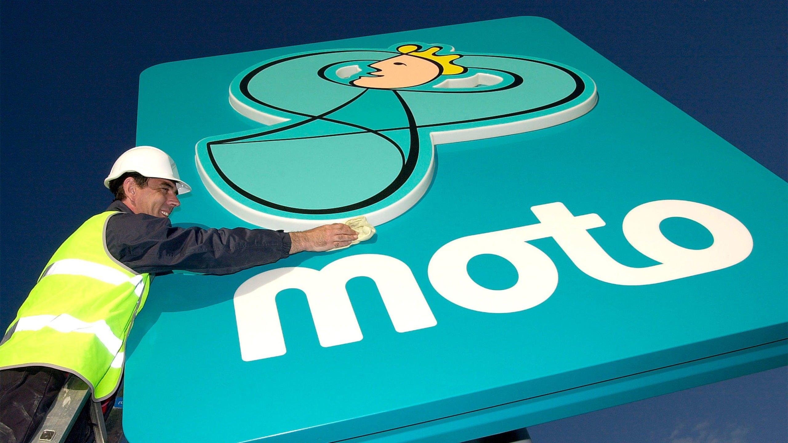 Man polishing large Moto sign