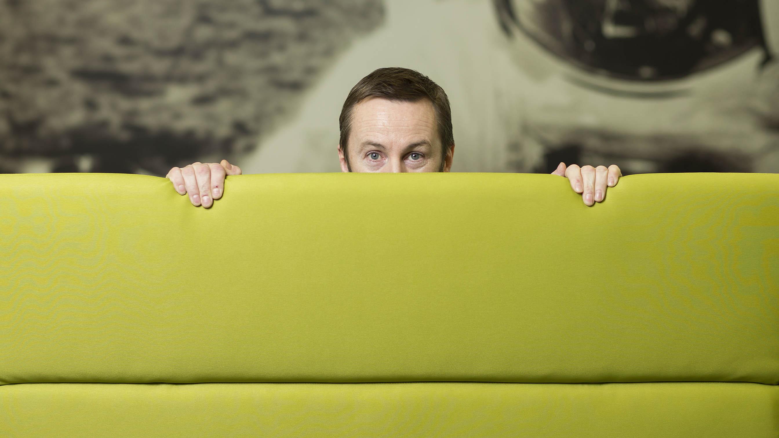 Man stood behind green screen with eyes visible